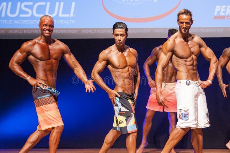 De mannelijke geschiktheidsmodellen tonen hun lichaamsbouw in zwempakom stadium stock afbeelding