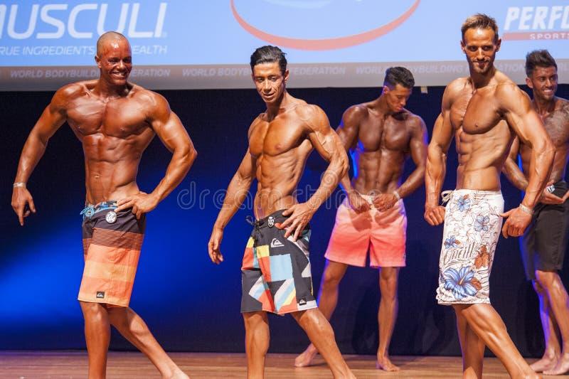 De mannelijke geschiktheidsmodellen tonen hun lichaamsbouw in zwempakom stadium stock foto's