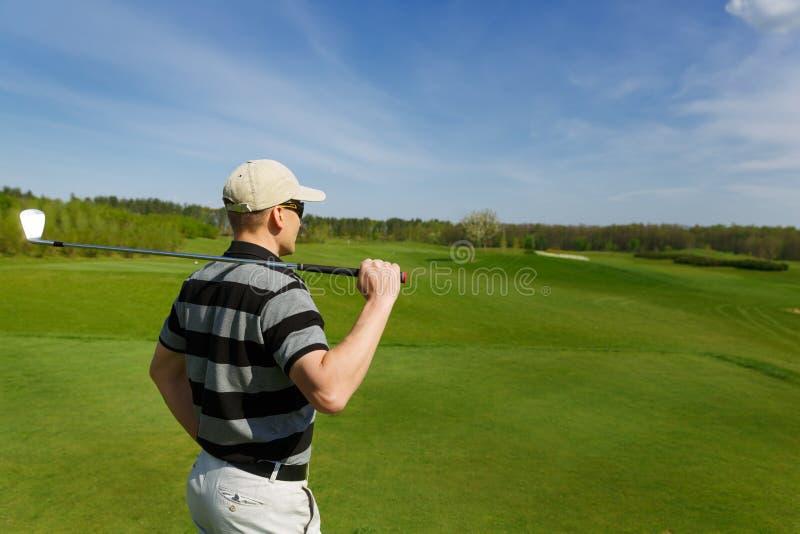 De mannelijke golfspeler ontspant tijdens een zonnige dag stock afbeelding