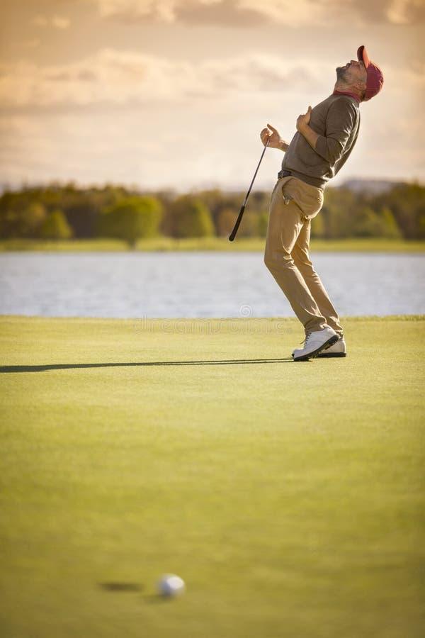De mannelijke golfspeler schoot afgelopen gat stock afbeeldingen