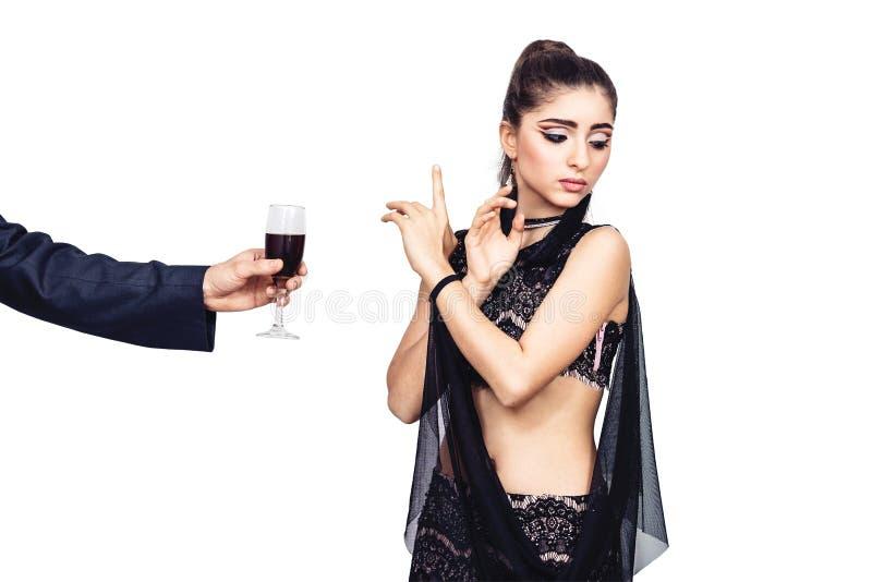 De mannelijke hand biedt een jong meisje een glas wijn aan De vrouw weigert om alcohol te drinken stock foto's