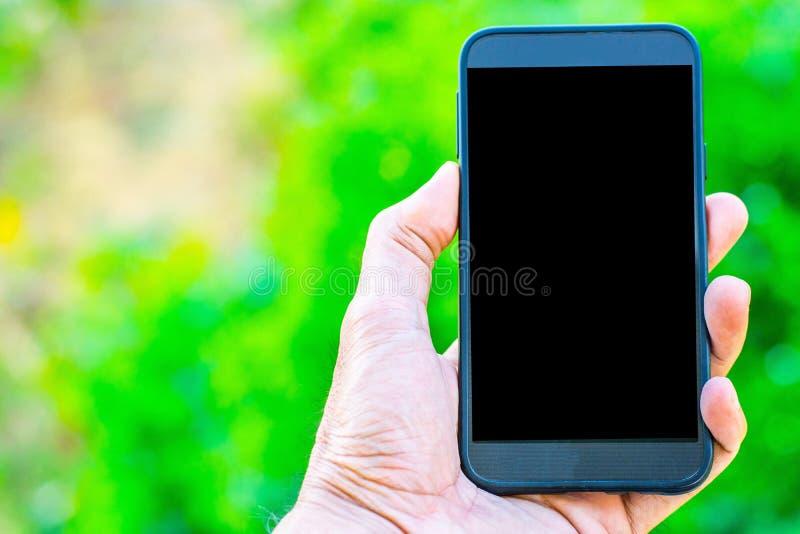 De mannelijke hand die een smartphone op een boom bokeh achtergrond een behang gebruiken of achtergrond die voor mededeling houde stock afbeeldingen