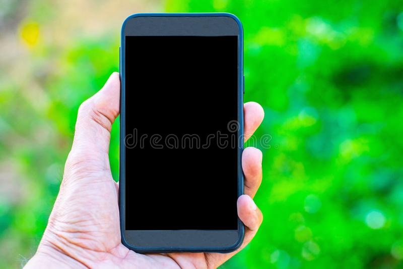 De mannelijke hand die een smartphone op een boom bokeh achtergrond een behang gebruiken of achtergrond die voor mededeling houde royalty-vrije stock fotografie