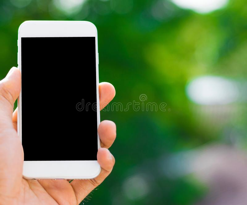 De mannelijke hand die een smartphone op een boom bokeh achtergrond een behang gebruiken of achtergrond die voor mededeling houde stock foto
