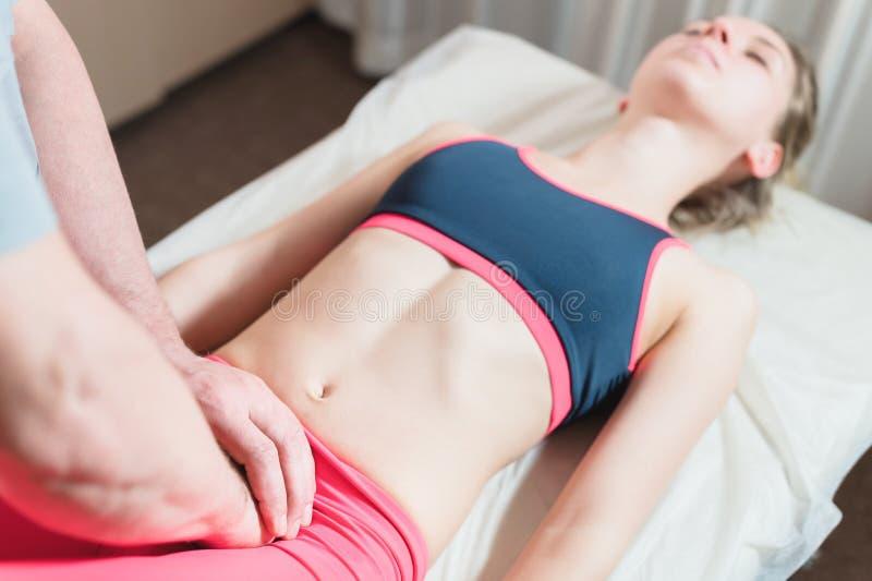 De mannelijke hand diepgewortelde therapeutmasseur behandelt een jonge vrouwelijke pati?nt Het externe uitgeven van de baarmoeder stock fotografie