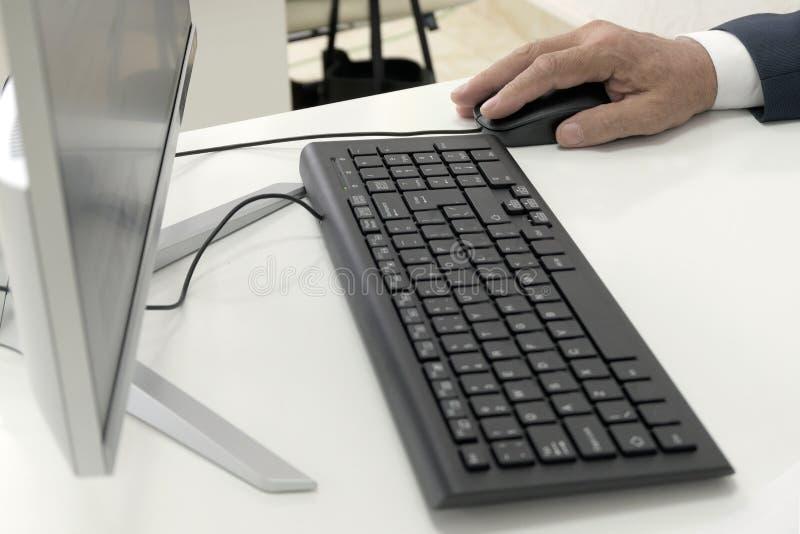De mannelijke hand houdt een muis naast het toetsenbord en de monitor van een personal computer op een witte lijst Close-up Een z stock afbeeldingen