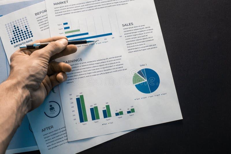 De mannelijke hand houdt een pen en richt aan de grafiek en de tekst op een wit blad van document dat ligt royalty-vrije stock afbeeldingen