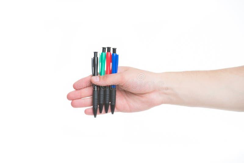 De mannelijke hand houdt vier pennen witte achtergrond isoleerden Het concept van de bureaukantoorbehoeften Hij altijd klaar om c royalty-vrije stock afbeelding