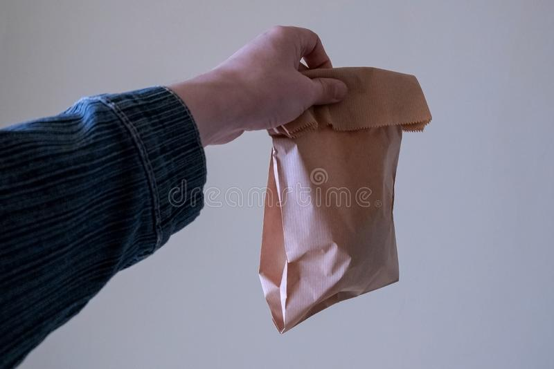 De mannelijke hand rekt een document zak met onbekende voorwaartse inhoud uit Het concept ecologische verpakking van voedsel, de  royalty-vrije stock afbeelding