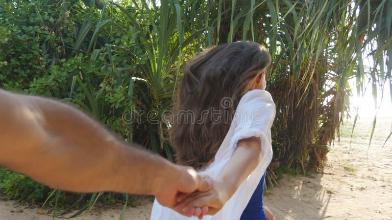 De mannelijke hand van de meisjesholding en het lopen op tropisch exotisch strand aan de oceaan Volg me schot van jonge vrouw tre stock fotografie
