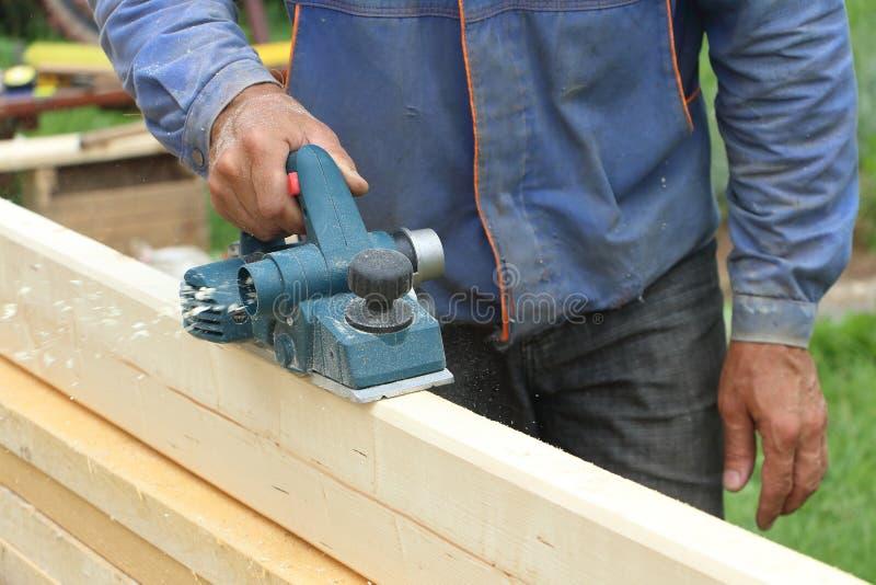 De mannelijke hand verwerkt een houten raad elektrische planer stock afbeeldingen