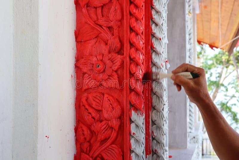 De mannelijke hand was geschilderd rood bij de Thaise tempelmuur stock foto's