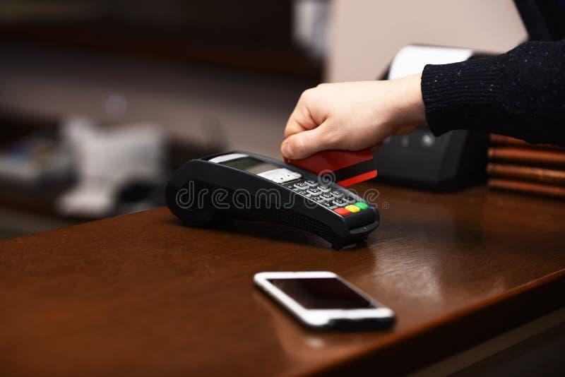 De mannelijke hand zet bankkaart in lezer defocused achtergrond stock afbeeldingen