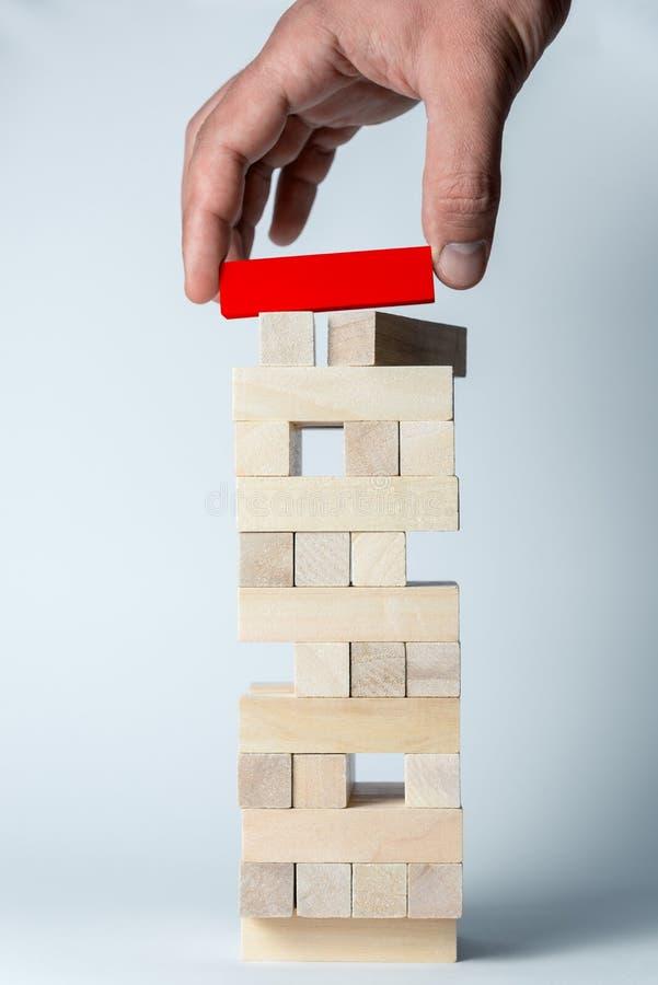 De mannelijke hand zet een rode kubus op de toren van houten kubussen, als symbool van steun, groepswerk en bedrijfsontwikkeling  stock foto