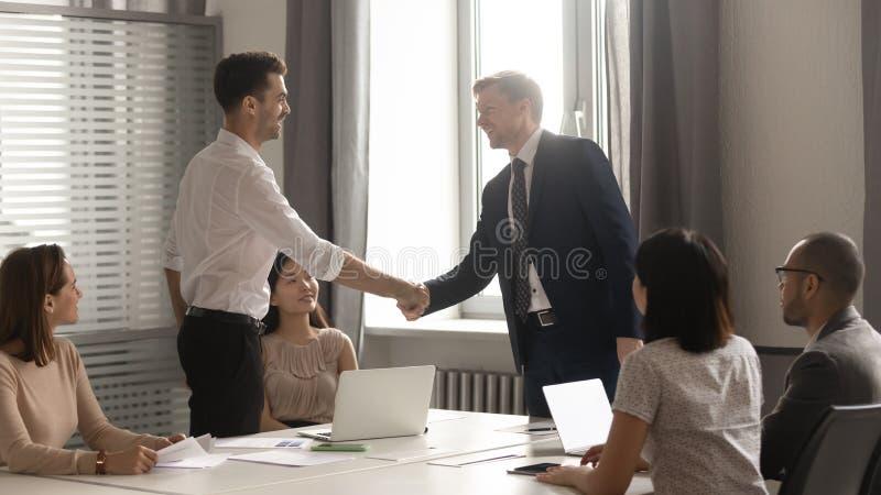 De mannelijke handdruk van partnersonderhandelaars bij de vergaderingsonderhandelingen van het groepsbureau royalty-vrije stock foto's