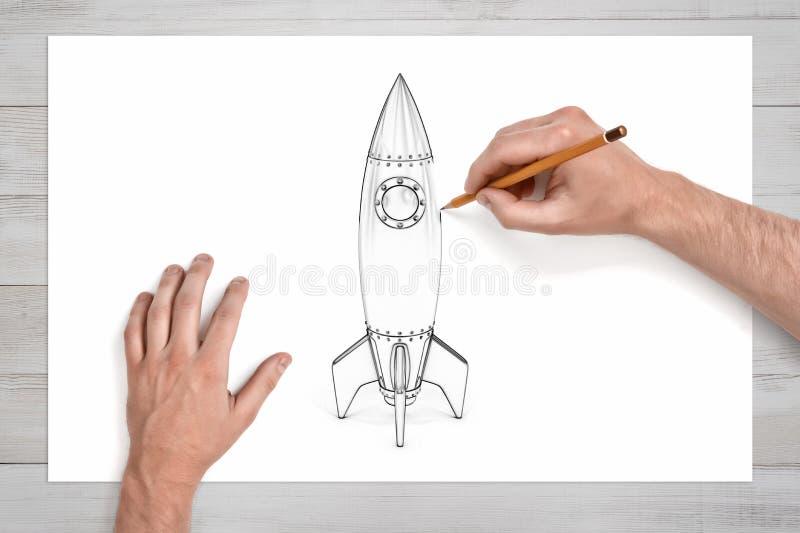 De mannelijke handen gebruiken een potlood om een ruimteraket met ronde illuminator te trekken stock afbeeldingen