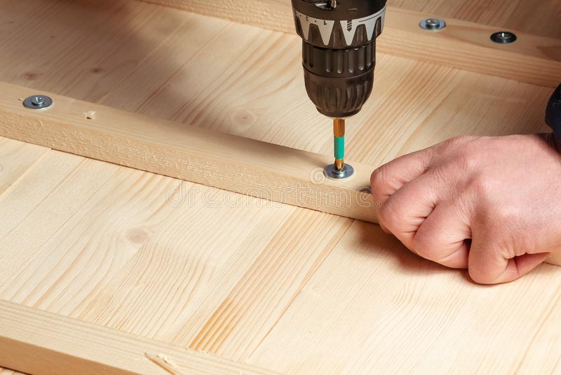 De mannelijke handen schroeven houten blokken aan de raad met een schroevedraaier stock foto's