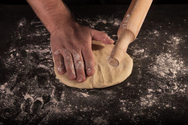De mannelijke handen van de chef-kok ontwikkelden het pizzadeeg op donkere lijst royalty-vrije stock fotografie