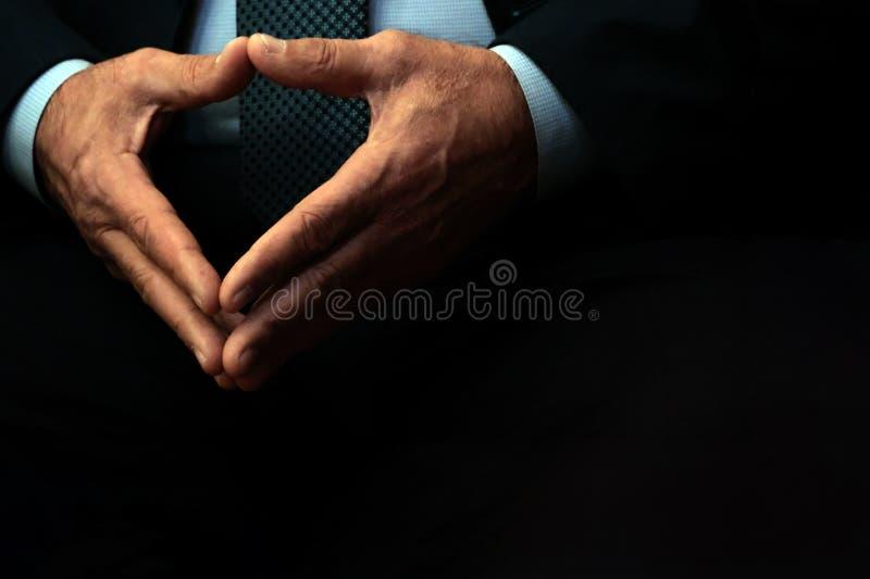 De mannelijke handen van een ambtenaar of een zakenman zijn gevouwen in een driehoek Zwarte achtergrond De ruimte van het exempla stock foto's