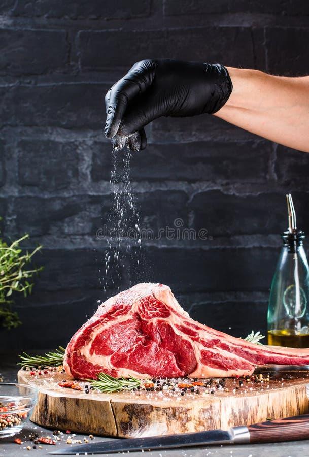 De mannelijke handen van slager of kok het rundvleeslapje vlees van de holdingstomahawk op donkere rustieke keuken dienen achterg stock afbeeldingen