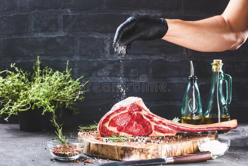 De mannelijke handen van slager of kok het rundvleeslapje vlees van de holdingstomahawk op donkere rustieke keuken dienen achterg royalty-vrije stock foto's