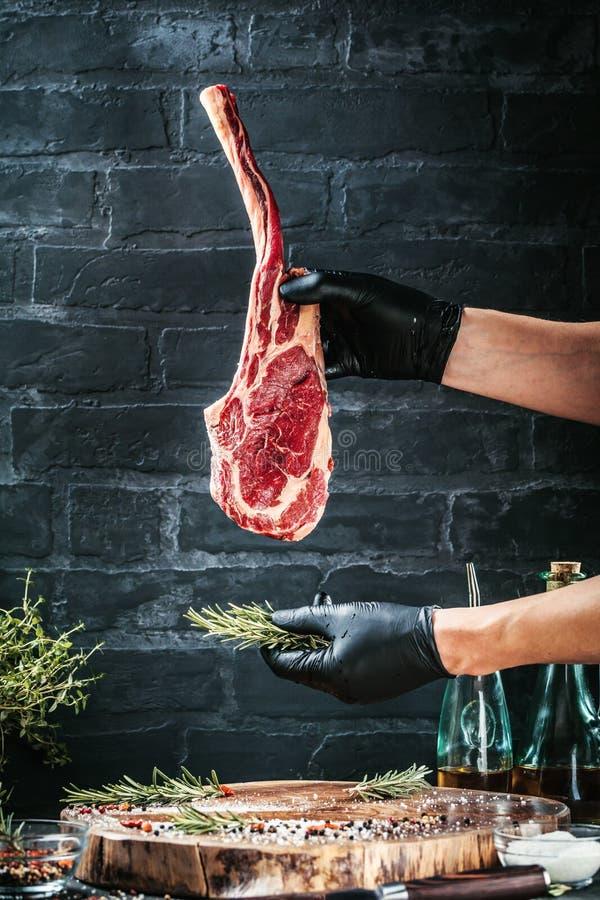 De mannelijke handen van slager of kok het rundvleeslapje vlees van de holdingstomahawk op donkere rustieke keuken dienen achterg royalty-vrije stock fotografie