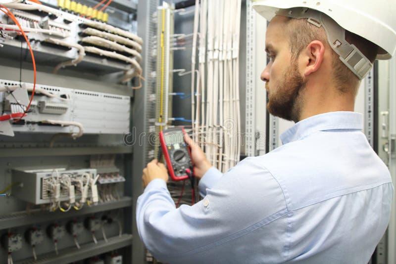 De mannelijke ingenieur controleert elektrosysteem met elektronische hulpmiddelen stock afbeelding