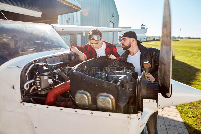 De mannelijke ingenieur en zijn zoon die het compartiment van de vliegtuigmotor bekijken, controleren vóór vlucht royalty-vrije stock afbeelding