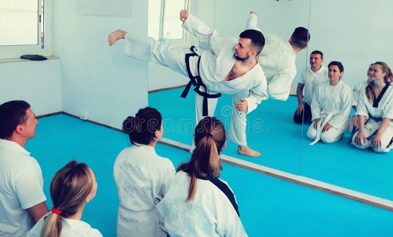 De mannelijke instructeur toont zijn vaardigheden in vechtsporten aan stock fotografie