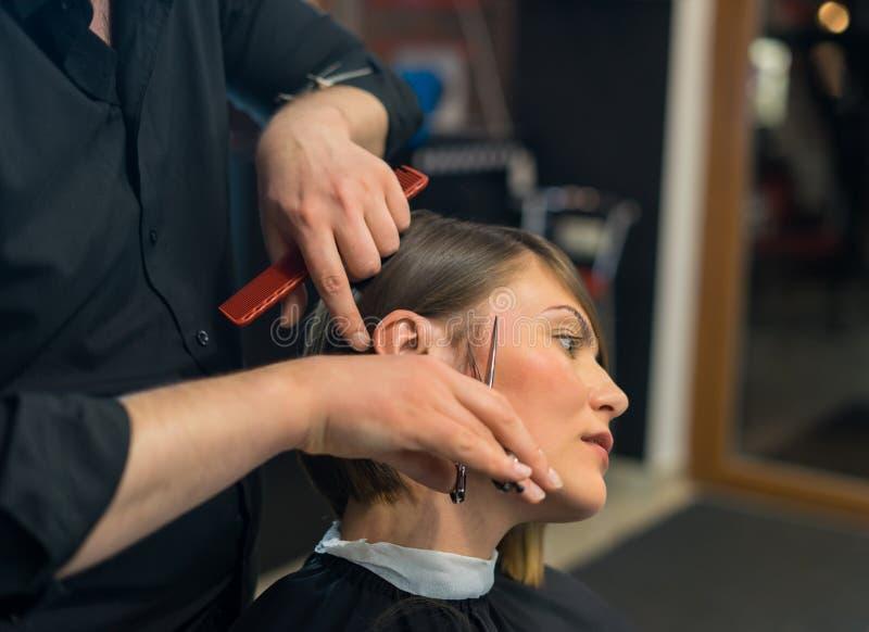 De mannelijke kapper doet een kapsel aan mooie vrouw royalty-vrije stock foto's