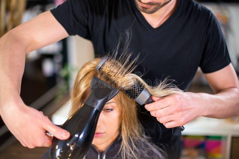 De mannelijke kapper droogt haar royalty-vrije stock fotografie