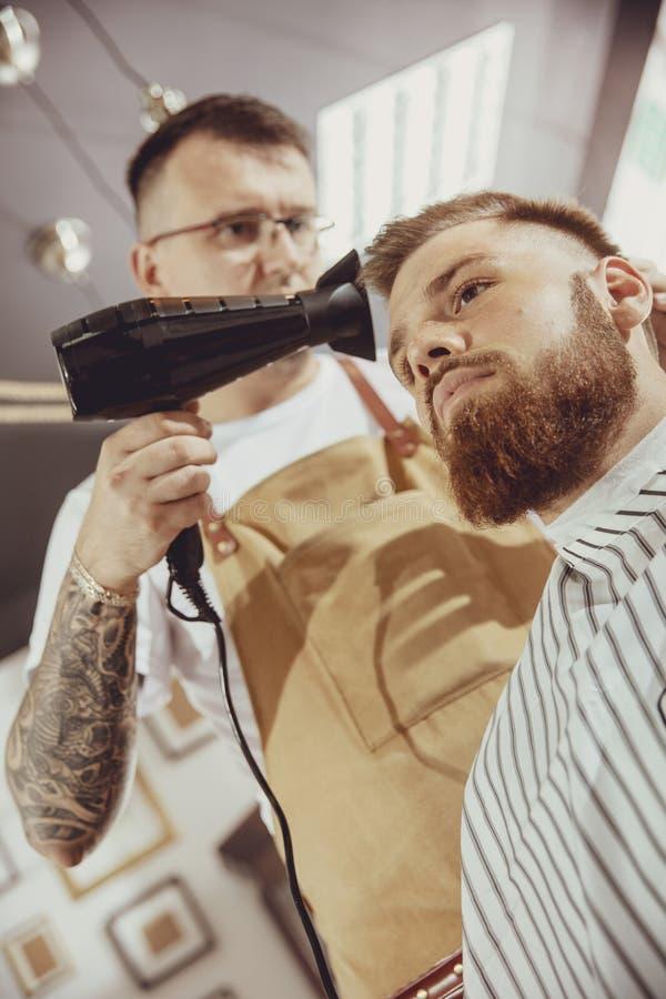 De mannelijke kapper droogt haar van zijn cliënt stock fotografie