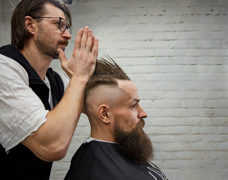 De mannelijke kapper maakt een mohawkkapsel gebruikend clipper van een volwassen mens met baard royalty-vrije stock afbeeldingen