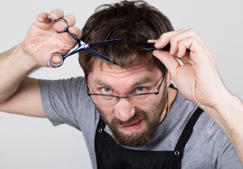 De mannelijke kapper snijdt zich, die de camera zoals de spiegel bekijken de modieuze professionele kapper drukt verschillend uit stock afbeeldingen