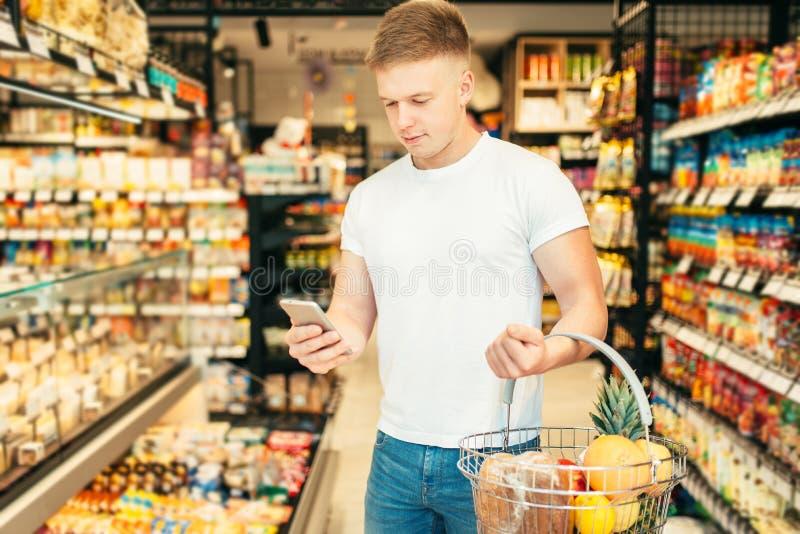 De mannelijke klant gebruikt mobiele telefoon in supermarkt stock fotografie