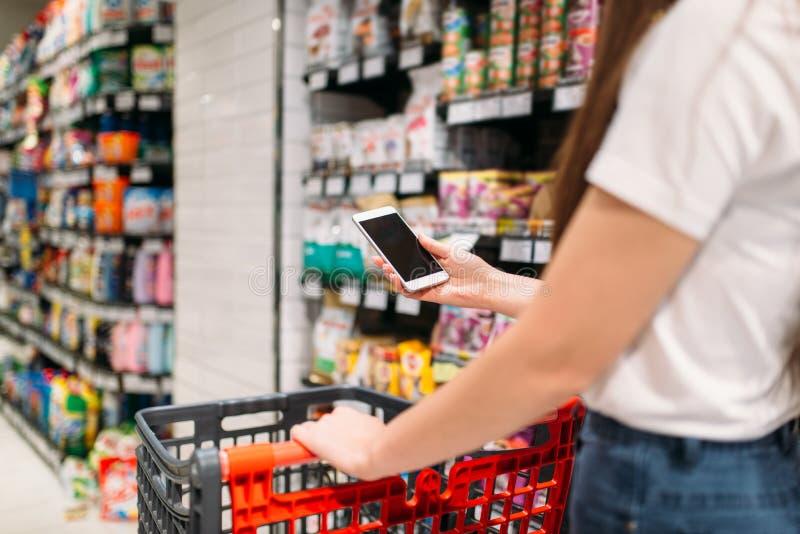 De mannelijke klant gebruikt mobiele telefoon in supermarkt royalty-vrije stock afbeelding
