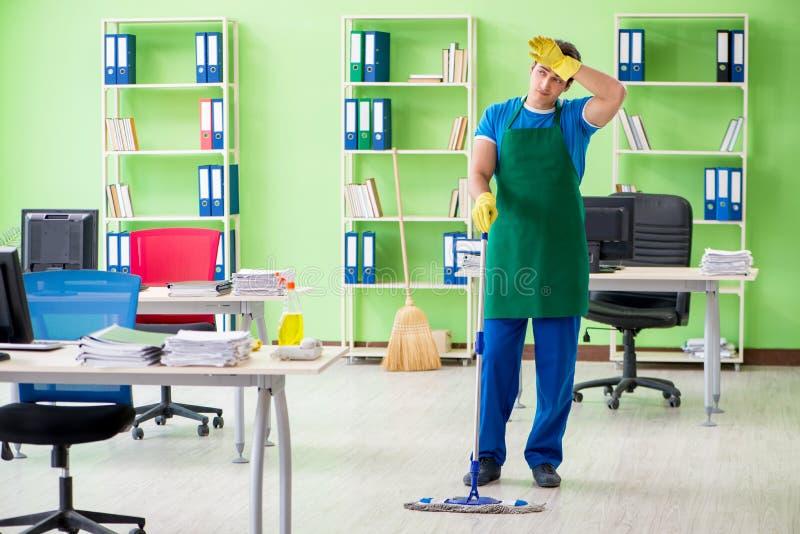 De mannelijke knappe professionele reinigingsmachine die het dweilen in het bureau doen royalty-vrije stock afbeelding