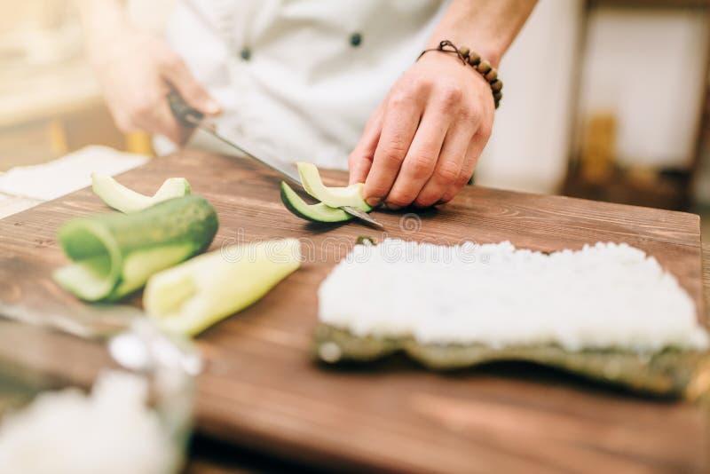 De mannelijke kok overhandigt close-up, makend sushibroodjes stock afbeelding