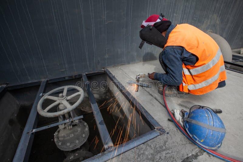 De mannelijke lasser last nieuwe staalrooster, booglassenprocédé met vonken Fabrieksarbeiderconcept Lange Blootstelling royalty-vrije stock foto's