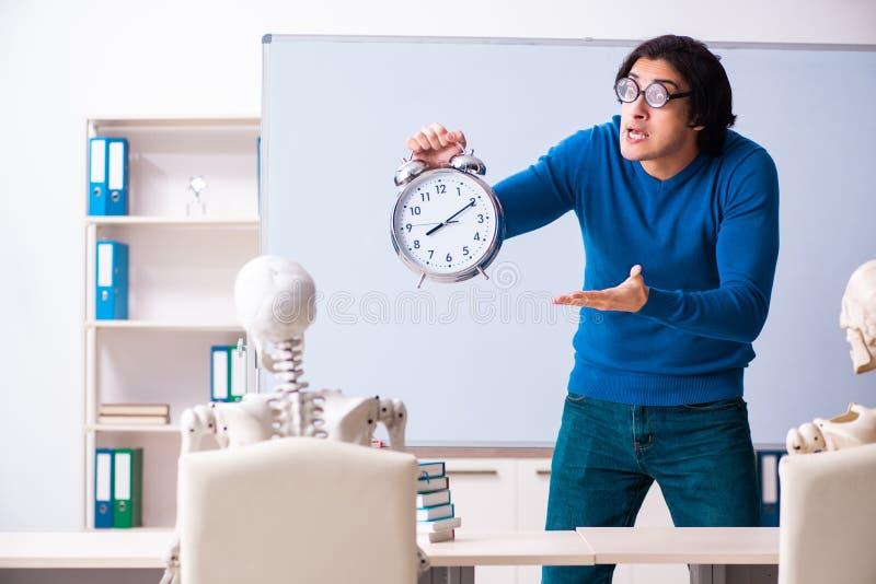 De mannelijke leraar en de skeletstudent in het klaslokaal royalty-vrije stock fotografie