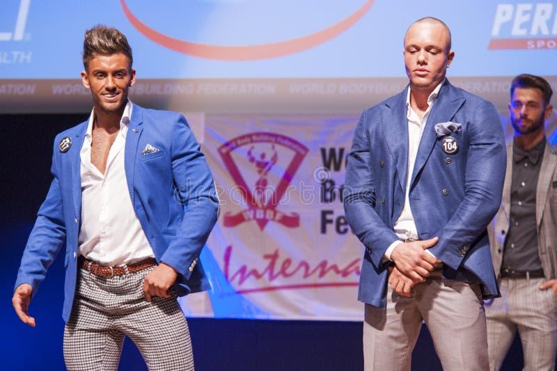 De mannelijke lichaamsbouwmodellen tonen hun beste in kostuum op stadium stock afbeeldingen