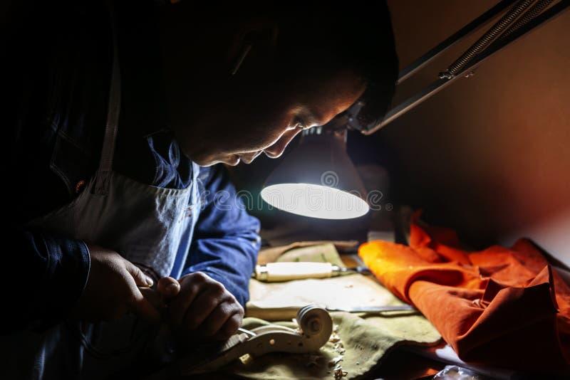 De mannelijke maker die van de vakmanviool aan een nieuwe viool werken stock fotografie