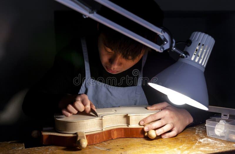 De mannelijke maker die van de vakmanviool aan een nieuwe viool werken royalty-vrije stock afbeelding