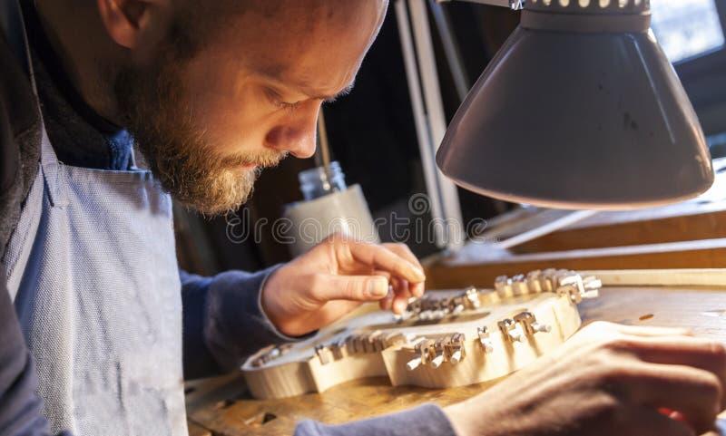 De mannelijke maker die van de vakmanviool aan een nieuwe viool werken stock foto