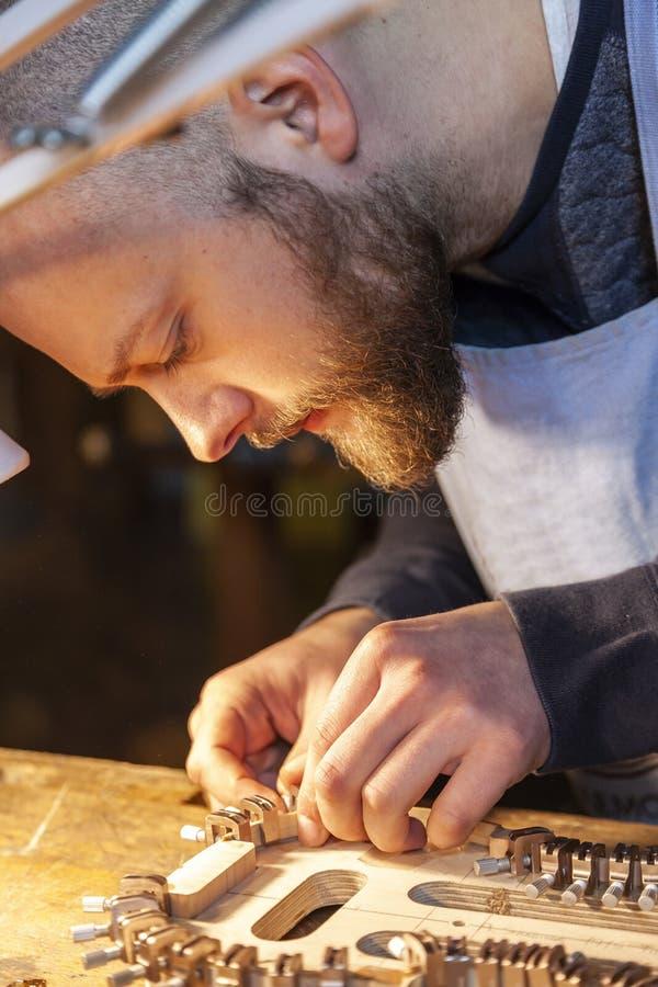 De mannelijke maker die van de vakmanviool aan een nieuwe viool werken stock afbeeldingen
