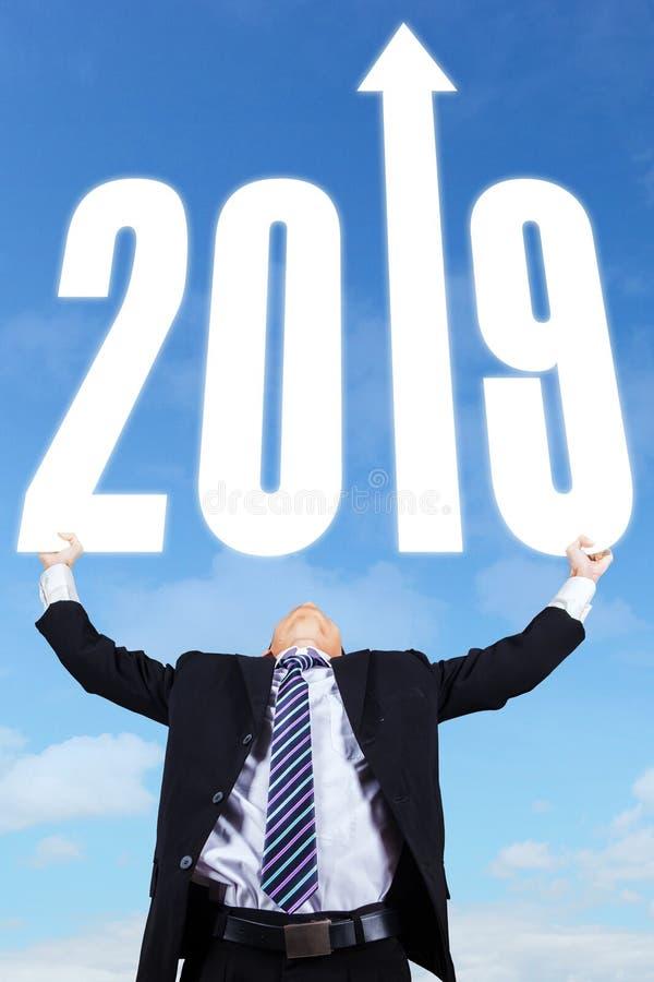De mannelijke manager houdt nummer 2018 en pijl stock afbeeldingen