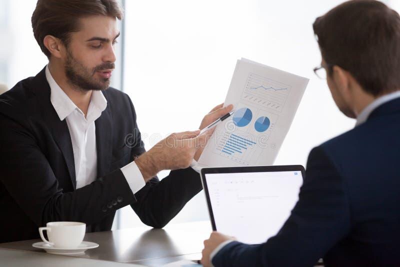 De mannelijke managers die bedrijf financiële statistieken analyseren tijdens komen samen royalty-vrije stock afbeeldingen