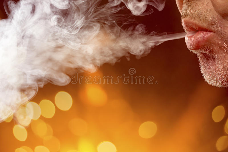 De mannelijke mond blaast uit rook royalty-vrije stock foto's