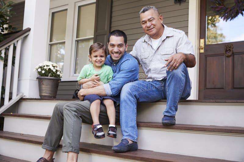 De mannelijke Multizitting van de Generatiefamilie op Stappen in Front Of House stock foto's