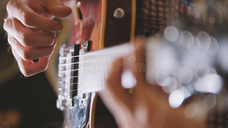 De mannelijke musicus speelt de gitaar, dicht omhoog overhandigt, nadruk op de gitaar fretboard stock fotografie